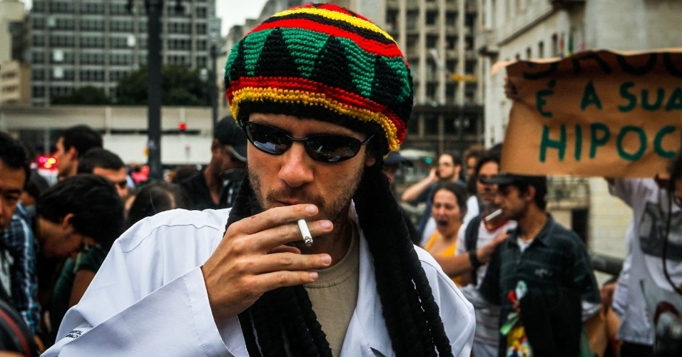 2.abr.2013 - Homem fuma cigarro que recebeu durante a Marcha da Maconha, realizada nesta terça-feira (2) no viaduto do Chá, centro de São Paulo