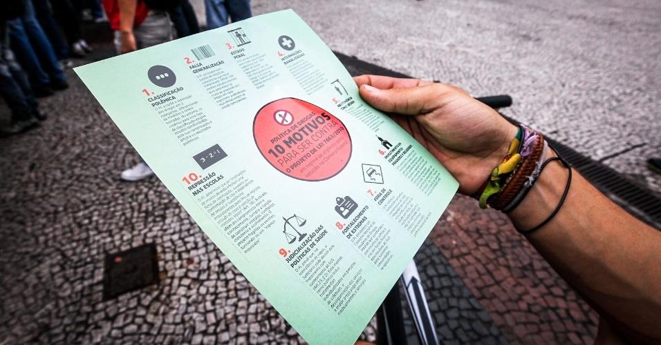 2.abr.2013 - Homem segura panfleto que aponta motivos para ser contra projeto de lei que propõe a obrigatoriedade de uma nova classificação das drogas, durante a Marcha da Maconha, no viaduto do Chá, no centro de São Paulo, na tarde desta terça-feira (2). A marcha pede a legalização da droga no país e é contrária à internação forçada de usuários de drogas