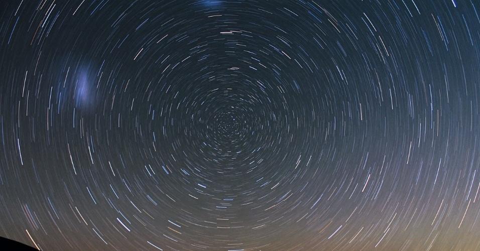"""2.abr.2013 - O Observatório Europeu do Sul (ESO, na sigla em inglês) divulgou uma bela vista dinâmica do céu noturno sobre a residência do Observatório do Paranal, no Chile. Para obter os rastros das estrelas, que ficam circulares devido à rotação da Terra, o fotógrafo Farid Char fez uma exposição de 30 minutos do cenário. Na imagem é possível ver o ponto """"parado"""" do polo Sul celeste (centro) e a Grande e a Pequena Nuvens de Magalhães, galáxias vizinhas à Via Láctea (manchas difusas à esquerda e em cima)"""