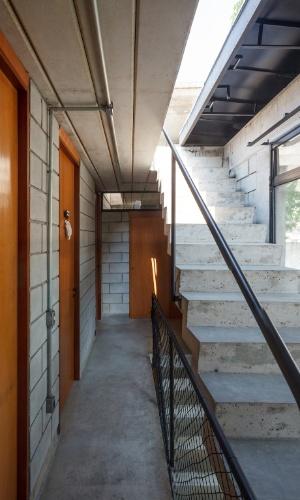 Vista do corredor de circulação dos dormitórios, no piso superior, com escada de acesso à cobertura, onde está o reservatório de água. A Casa Maracanã tem projeto arquitetônico assinado pelo escritório Terra e Tuma