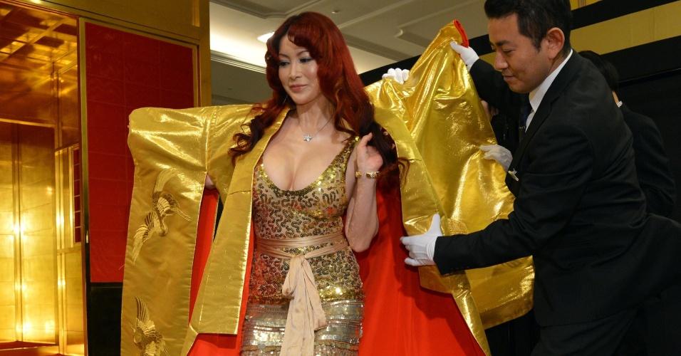 3.abr.2013 - A japonesa Mika Kano usa um manto nupcial tecido por fibras feitas de ouro que é comercializado na ?Expo Gold?, em Tóquio, por R$ 1,13 milhão, nesta quarta-feira. A exposição pretende vender um total de R$ 263 milhões em produtos feitos de ouro, incluindo uma barra de 120 kg cujo preço é de R$ 13 milhões