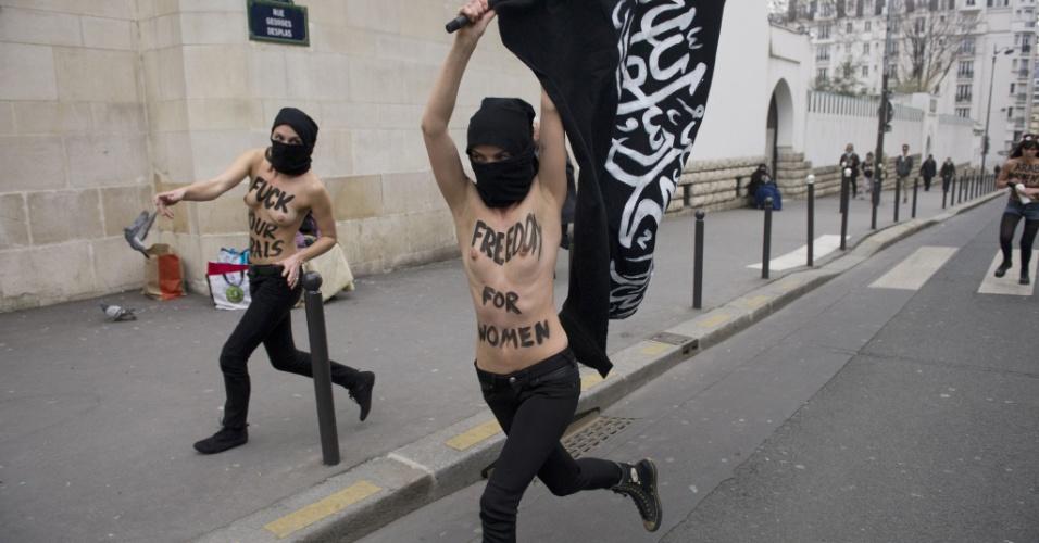 3.abr.2013 - Ativistas do Femen queimam bandeira salafista (movimento ultraortodoxo que pretende viver o islã como nos tempos do profeta) em protesto realizado em frente a mesquita em Paris