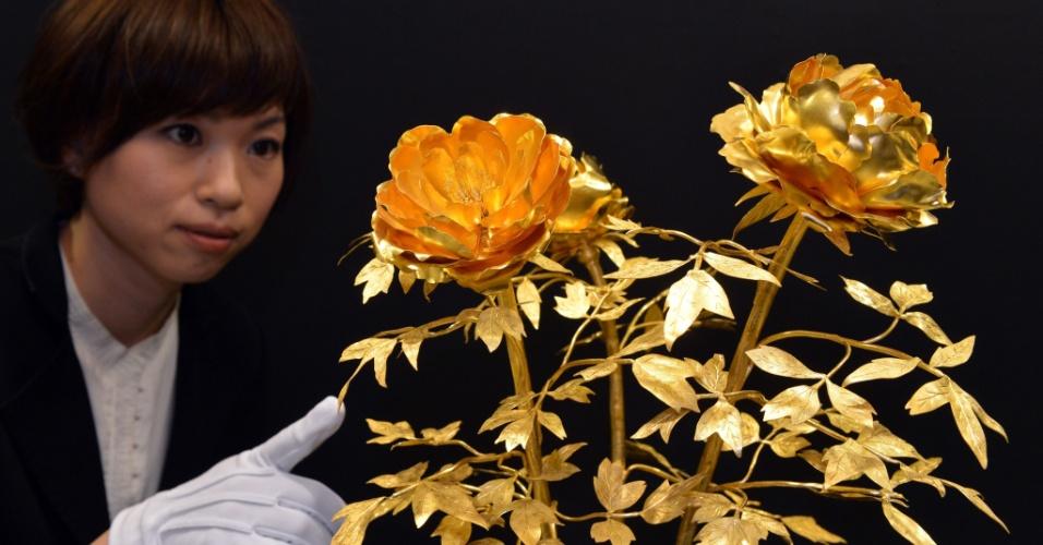 3.abr.2013 - Funcionário de loja onde acontece a ?Expo Ouro?, em Tóquio, apresenta arranjo floral feito de ouro puro, que pesa 4,2 kg e custa R$ 3,4 milhões. A exposição pretende vender um total de R$ 263 milhões em produtos feitos de ouro, incluindo uma barra de 120 kg cujo preço é de R$ 13 milhões