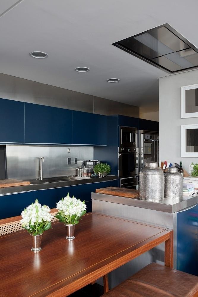 Com a demolição da parede, a cozinha ficou totalmente integrada ao living e possui mobiliário azul planejado pela Brinna. Destaque para o forro rebaixado em gesso que embute a coifa retangular. O projeto de reforma do loft Itaim foi criado pelo escritório FGMF Arquitetos