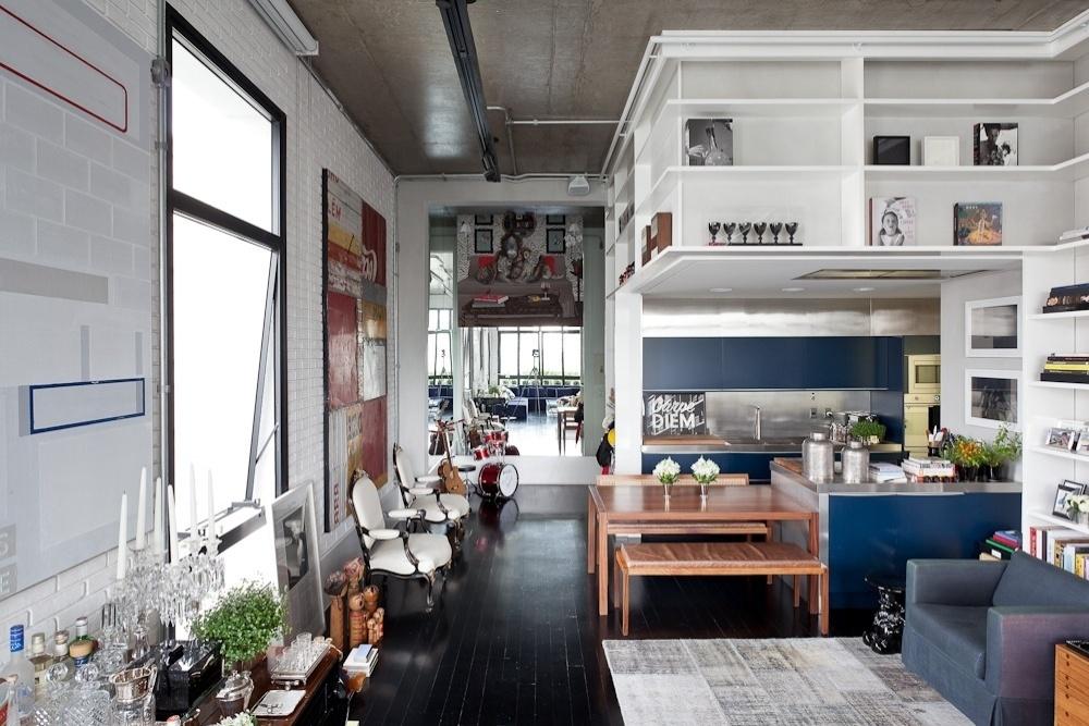 O loft Itaim, com projeto de reforma do escritório FGMF Arquitetos, apresenta pé-direito de 4,50 m que foi aproveitado para a instalação de uma estante que se prolonga sobre a cozinha. Piso ebanizado e teto em concreto aparente proporcionam interessante contraste