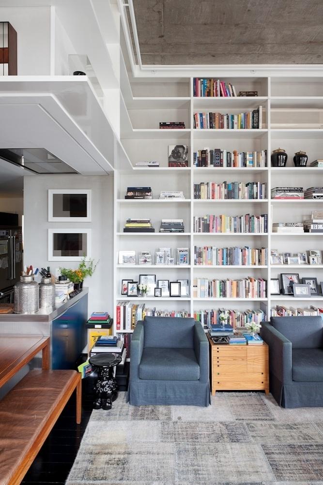 O projeto de reforma do loft Itaim, assinado pelo escritório FGMF Arquitetos, se destaca pela criatividade ao ocupar uma parede inteira com uma estante de quatro metros de altura. O tapete mesclado atual combina com as poltronas azuis pertencentes à família da proprietária