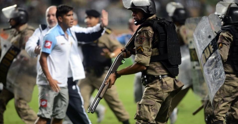 03.abr.2013 - Policial com a arma em punho durante confusão com jogadores do Arsenal de Sarandi no jogo do Atlético-MG