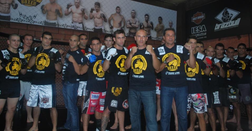 04.04.2012 - Luxa posa ao lado de lutadores de MMA em CT em Porto Alegre