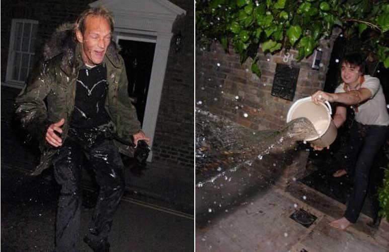 19.abr.2007: Irritado com os paparazzi na porta de sua casa e na de Kate Moss, Pete Doherty abre a porta e joga um balde de água nos fotógrafos