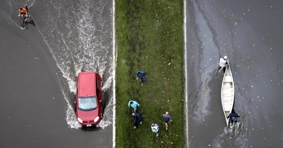 4.abr.2013 - Carro e bote percorrem rua alagada após temporal que causou inundações em quase toda a cidade de La Plata (Argentina). Pelo menos 54 morreram em decorrência das fortes chuvas que afetam a região desde a última terça-feira (2)
