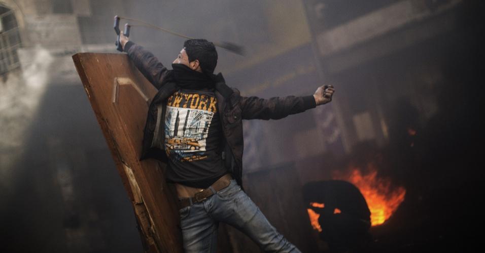 4.abr.2013 - Manifestante palestino usa um estilingue para atirar pedras por trás de barricada durante confrontos com soldados israelenses em Hebron, na Cisjordânia, nesta quinta-feira (4). Milhares de pessoas compareceram aos funerais de um preso falecido em Israel e de dois jovens mortos por disparos do exército israelense em um clima de grande tensão e revolta nos territórios palestinos