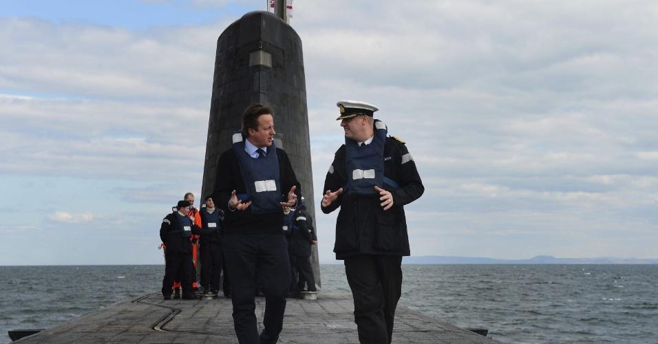 4.abr.2013 - O primeiro-ministro britânico, David Cameron (à esq.) caminha, acompanhado de um oficial militar, sobre o submarino nuclear Trident HMS Victorious, que navega na costa de Glasgow, no Reino Unido