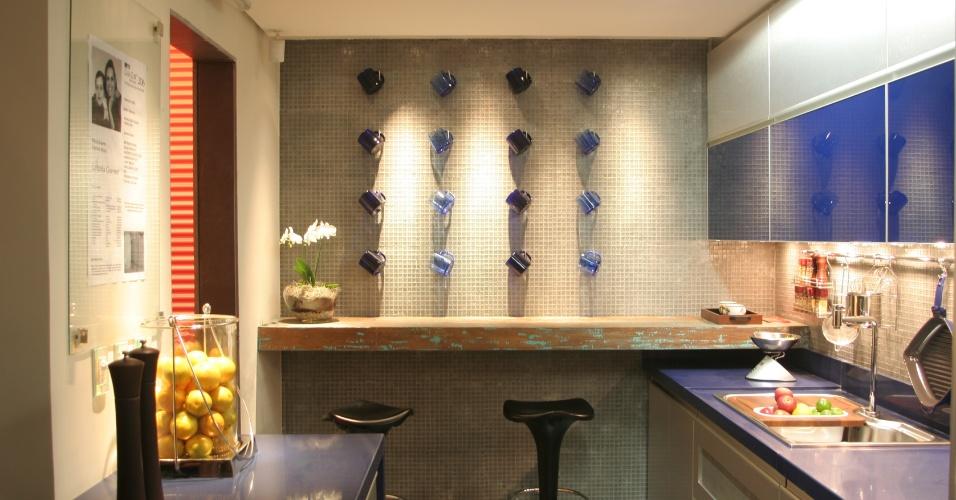 Na cozinha desenhada pelas arquitetas Flávia Soares e Patrícia Abreu, sobre as pastilhas de vidro que revestem toda a parede, as canecas na cor azul deixam o ambiente ainda mais charmoso