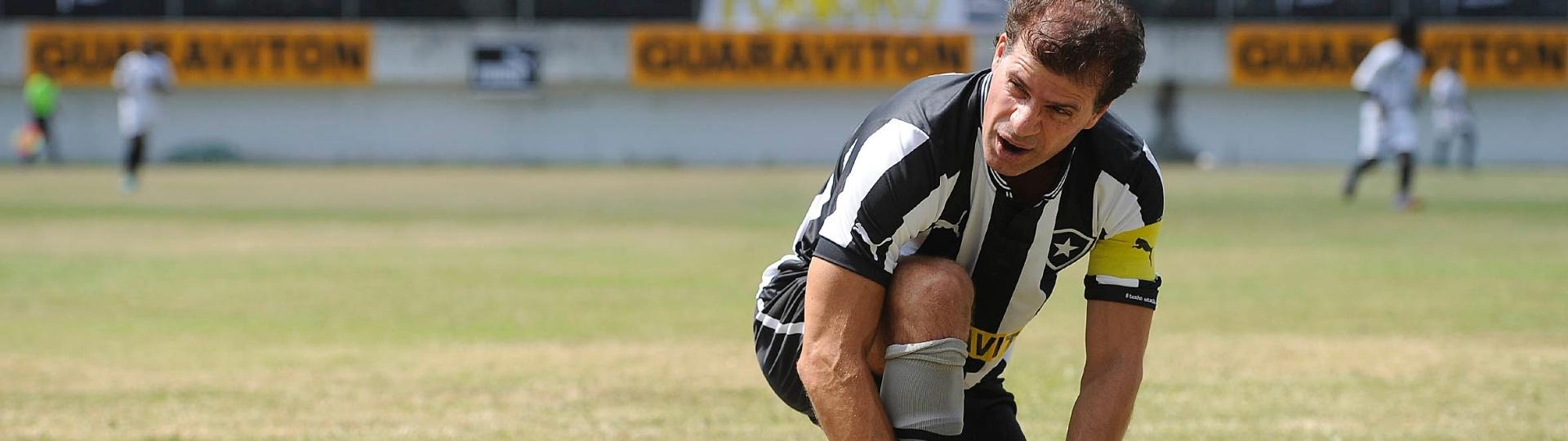 Túlio amarra chuteira durante amistoso entre Botafogo e Santos de Angola