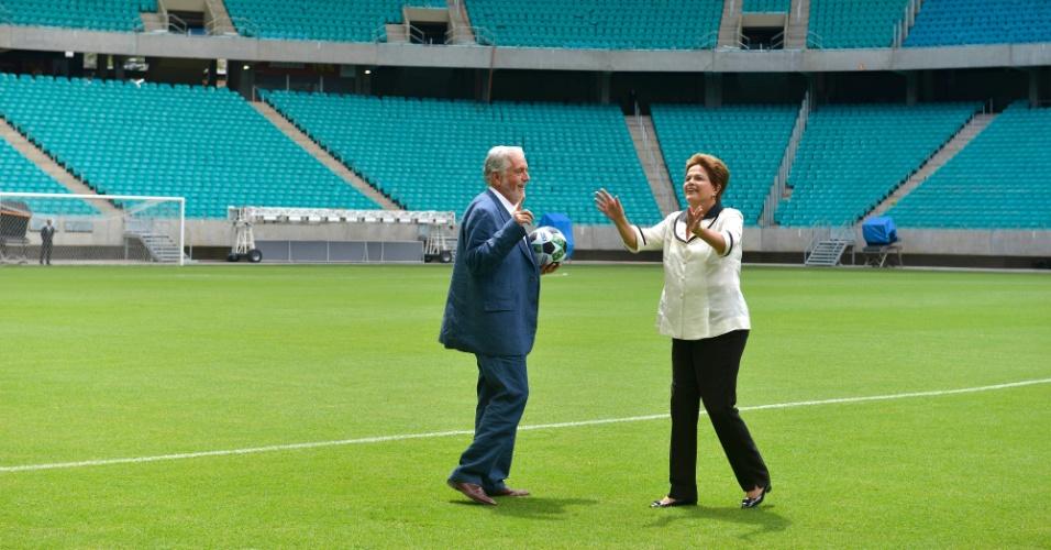 05.abr.2013 - O governador da Bahia, Jaques Wagner, leva a bola para o pontapé inicial de Dilma Rousseff na Arena Fonte Nova