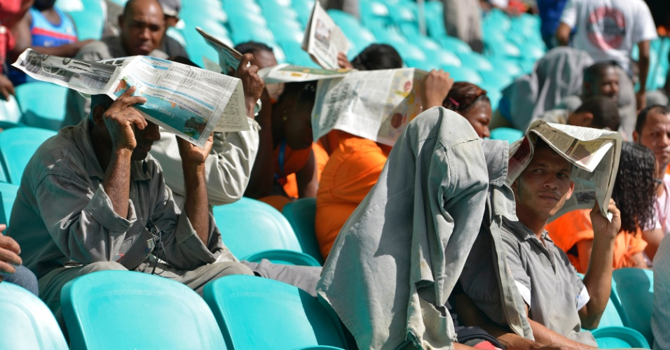 05.abr.2013 - Operários aguardam inauguração da Arena Fonte Nova sob forte sol, nas arquibancadas do novo estádio