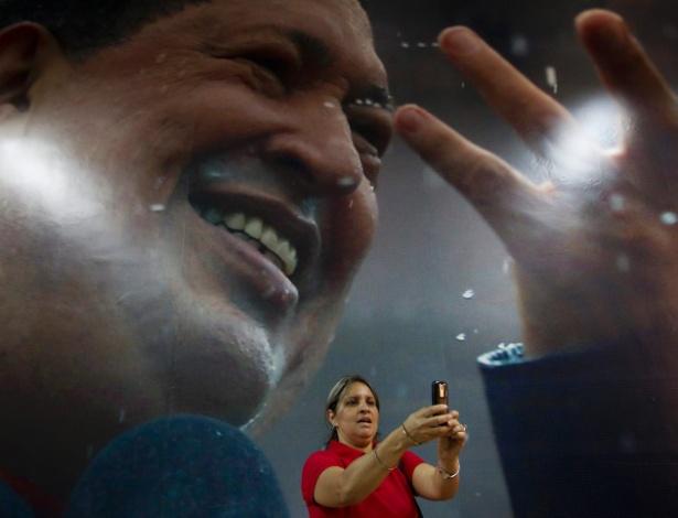 5.abr.2013 - Mulher tira fotografia em frente a uma imagem do falecido presidente venezuelano Hugo Chávez em forte militar de Caracas. O Quartel da Montanha, onde Chávez está enterrado, foi transformado em santuário e museu em homenagem ao ex-presidente. O país está em plena corrida eleitoral para escolher quem irá sucedê-lo