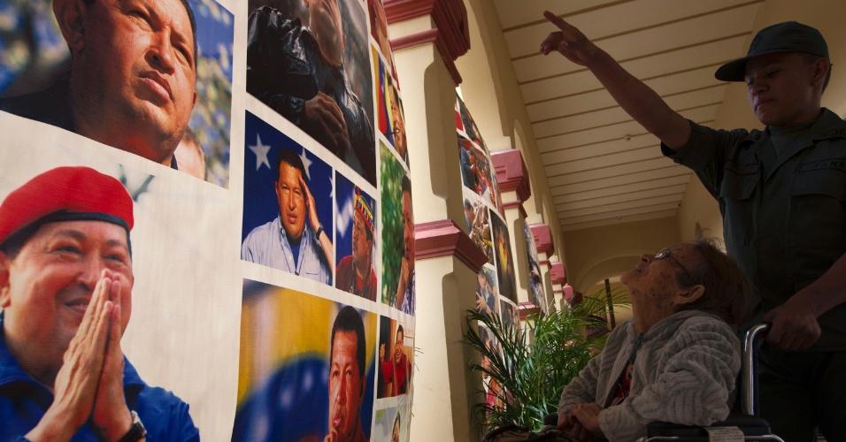 5.abr.2013 - Soldado guia idosa por galeria de fotos do falecido líder venezuelano Hugo Chávez em forte militar de Caracas. O Quartel da Montanha, onde Chávez está enterrado, foi transformado em santuário e museu em homenagem ao ex-presidente. O país está em plena corrida eleitoral para escolher quem irá sucedê-lo