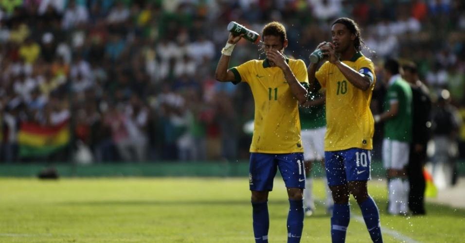 06.abr.2013 - Dupla Neymar e Ronaldinho Gaúcho se refresca durante o amistoso entre Brasil e Bolívia