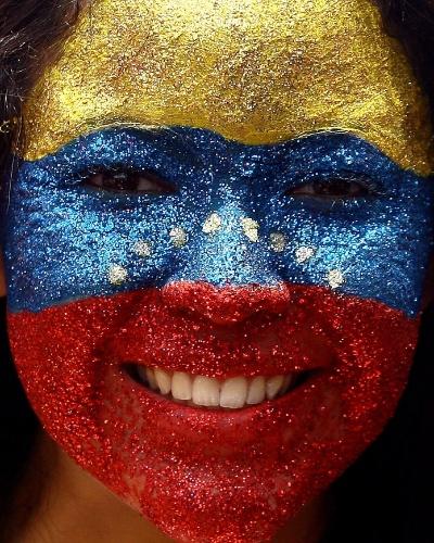 7.abr.2013 - Apoiadora de Capriles pinta o rosto em comício da campanha eleitoral para presidência da República em Caracas, capital da Venezuela, neste domingo (7)