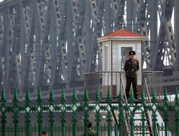 Guarda de fronteira patrulha ponte do rio Yalu, fronteiriço da China com a Coreia do Norte, na cidade chinesa de Dandong