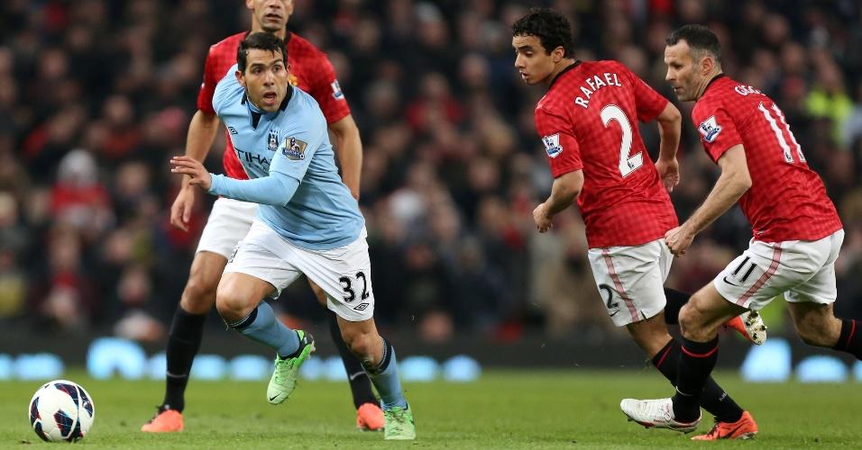 08.abr.2013 - Carlitos Tevez (esq), do Manchester City, tenta escapar da marcação do brasileiro Rafael durante clássico contra o Manchester United, pelo Campeonato Inglês