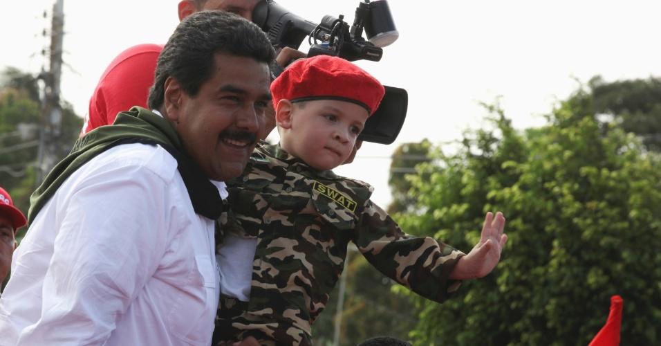 8.abr.2013 - O presidente interino da Venezuela, e candidato nas eleições presidenciais de 14 de abril, Nicolás Maduro, segura uma criança vestida em uniforme militar durante evento de campanha em Cumana, no Estado de Sucre (Venezuela), nesta segunda-feira (8)