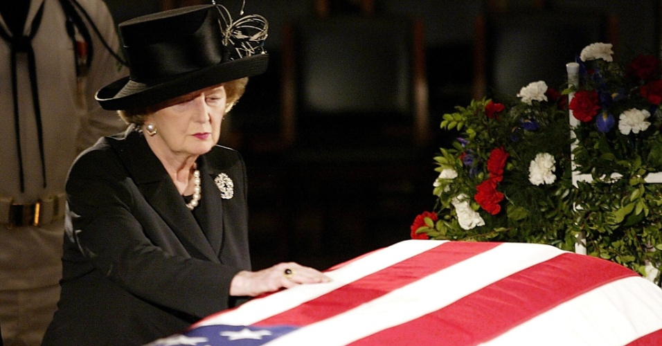 9.jun.2004 - Margaret Thatcher encosta em bandeira no caixão com o corpo do ex-presidente dos Estados Unidos Ronald Reagan. Thatcher foi primeira-ministra do Reino Unido de 1979 a 1990, o maior período contínuo no governo para um primeiro-ministro britânico desde o início do século 19