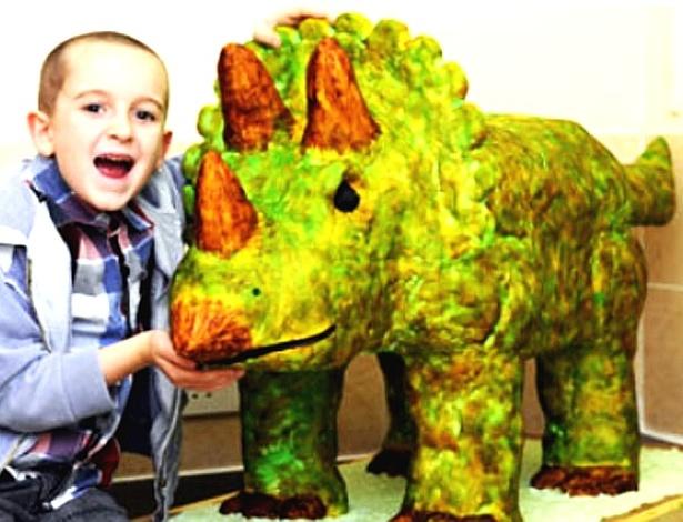 Não vai mimar o garoto! Logan, 8, ganhou da mãe um bolo em formato de dinossauro de 1,3 metro de comprimento para sua festinha