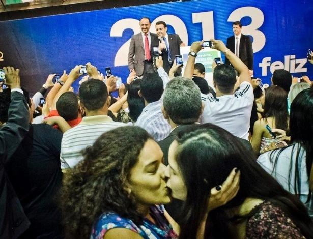 """6.abr.2013 - Duas mulheres se beijam durante culto evangélico celebrado pelo deputado e pastor Marco Feliciano (ao fundo), no Centro de Convenções Vale da Bênção, em Belém, no sábado (6). O ato foi um protesto contra o deputado, acusado de ser racista e homofóbico, ocupar a presidência da Comissão de Direitos Humanos da Câmara. Publicada nas redes sociais, a imagem provocou críticas pela """"falta de respeito"""" do ato ter sido realizado durante um culto religioso. Críticos de Feliciano apoiaram o protesto"""