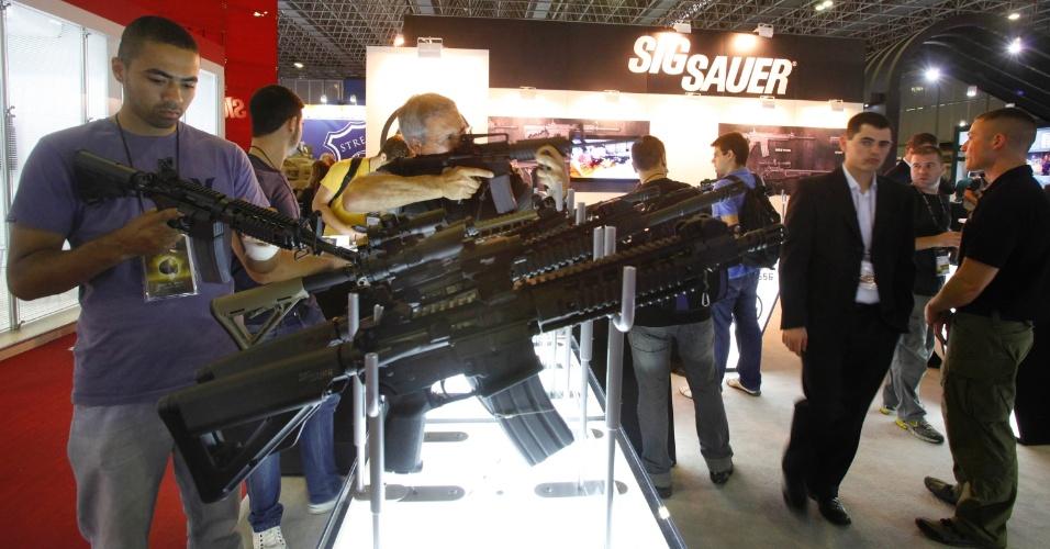 9.abr.2013 - Visitantes manuseiam armas em exibição na Feira Internacional de Defesa e Segurança LAAD Defence & Security, no Rio de Janeiro, a maior exposição de equipamentos militares da América Latina