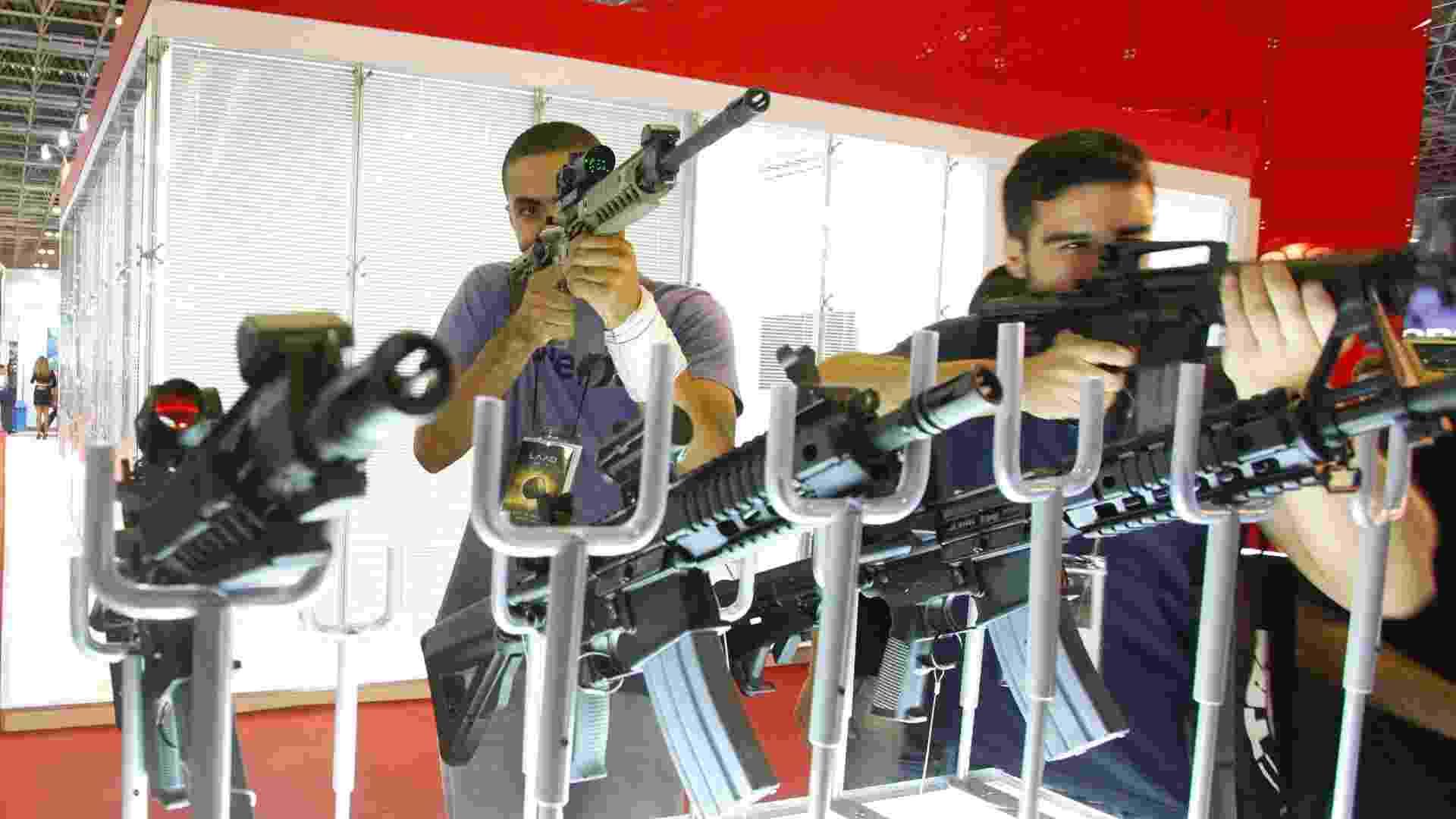 9.abr.2013 - Visitantes manuseiam armas em exibição na Feira Internacional de Defesa e Segurança LAAD Defence & Security, no Rio de Janeiro, a maior exposição de equipamentos militares da América Latina - Marco Antônio Teixeira/UOL