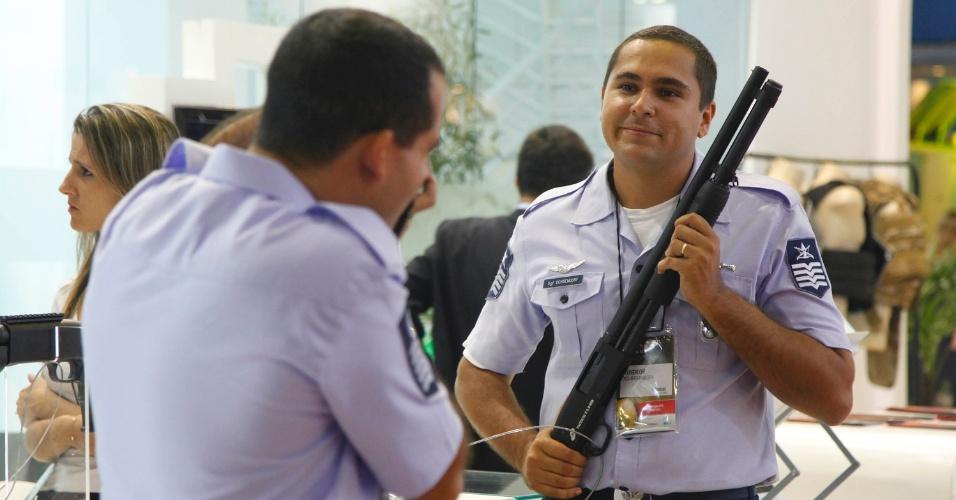 9.abr.2013 - Visitantes posam com armas em exibição na Feira Internacional de Defesa e Segurança LAAD Defence & Security, no Rio de Janeiro, a maior exposição de equipamentos militares da América Latina
