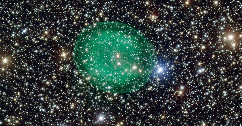 10.abr.2013 - Novas observações da nebulosa planetária IC 1295 mostram que a anã-branca que essa bolha verde rodeia está perto da morte: o pequeno ponto azul no centro é o que resta do núcleo queimado da estrela. As nebulosas planetárias são bolhas formadas pelo gases da atmosfera de estrelas massivas que foram expelidos após fusões instáveis. Já o brilho resulta da intensa radiação ultravioleta emitida pela anã-branca, tendo diferentes cores para os elementos químicos. No caso da IC 1295, que fica na constelação do Escudo, a 3.300 anos-luz de distância da Terra, o tom esverdeado surge do oxigênio ionizado. As imagens foram feitas com o telescópio VLT, localizado no Cerro Paranal, no Chile, do Observatório Europeu do Sul (ESO, na sigla em inglês)