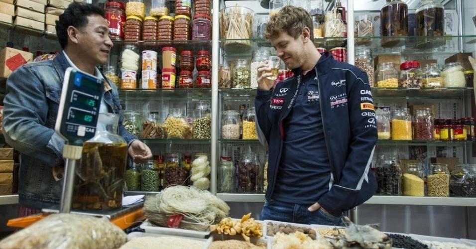 10.abr.2013 - Sebastian Vettel prova licor de serpente durante visita a um mercado de Xangai antes da corrida no final de semana