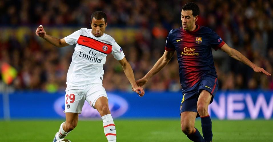 10.abr.2013- Lucas tenta escapar da marcação de Sergio Busquets durante jogo entre Barcelona e PSG, pelas quartas de final da Liga dos Campeões