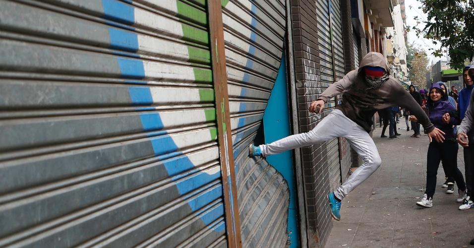 11.abr.2013 - Manifestante chuta porta durante manifestação que reuniu milhares de chilenos nesta quinta-feira (11). A marcha percorreu as ruas de Santiago para exigir uma educação pública gratuita e de melhor qualidade