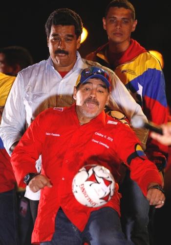 11.abr.2013 - O presidente interino da Venezuela, Nicolás Maduro (no fundo), observa o ex-jogador argentino de futebol Diego Maradona chutar uma bola durante comício em Caracas, nesta quinta-feira (11), último dia da campanha presidencial na Venezuela. O chavista Maduro concorre contra o líder da oposição Henrique Capriles nas eleições deste domingo (14)