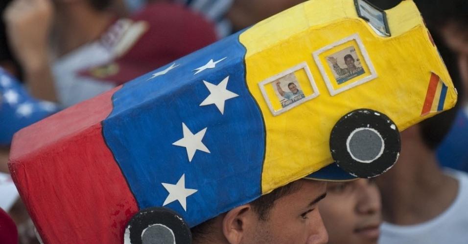 11.abr.2013 - Apoiador do candidato da oposição às eleições da Venezuela, Henrique Capriles, usa um chapéu em formato de ônibus durante comício de encerramento de campanha em Barquisimeto, no Estado de Lara. No próximo domingo (14) será eleito o primeiro presidente eleito da era pós-Hugo Chávez