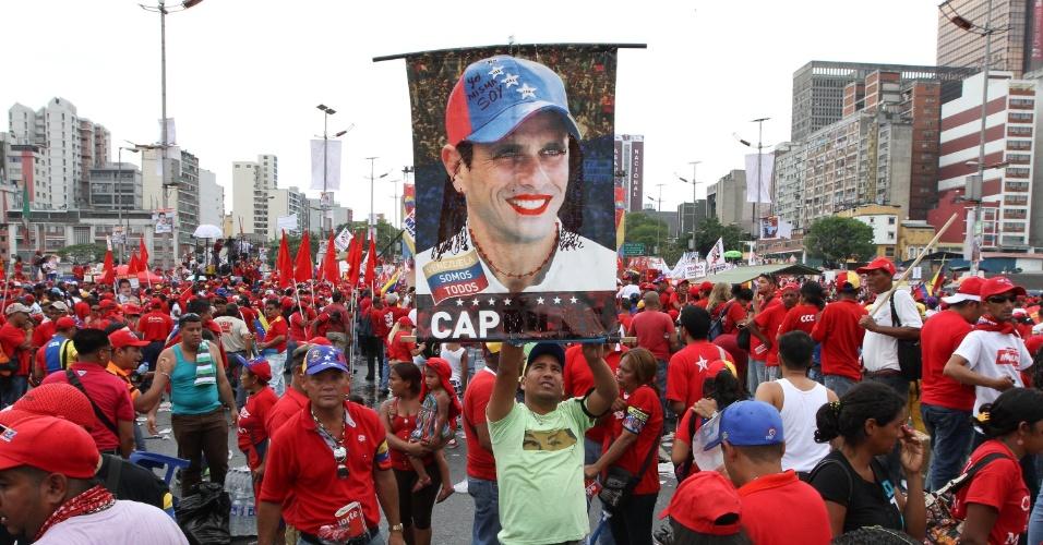 11.abr.2013 - Apoiadores do candidato governista à eleições da Venezuela, Nicolás Maduro, seguram placa com foto do candidato da oposição, Henrique Capriles, com a boca pintada de vermelho, durante durante comício de encerramento de campanha em Caracas. No próximo domingo (14) será eleito o primeiro presidente eleito da era pós-Hugo Chávez