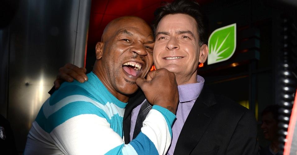 12.abr.2013 - Mike Tyson simula um golpe no queixo do ator Charlie Sheen e uma mordida em sua orelha durante a pré-estreia da comédia