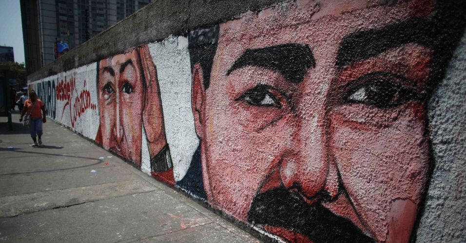 12.abr.2013 - Pedestre caminha próximo a mural com desenho do candidato governista à presidência da Venezuela e presidente em exercício Nicolás Maduro, ao lado de seu antecessor, Hugo Chávez. No próximo domingo (14) será eleito o primeiro presidente eleito da era pós-Hugo Chávez