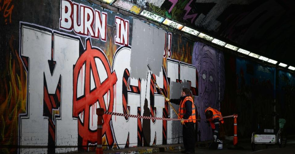 12.abr.2013 - Trabalhadores pintam parte do grafite em que se lia a palavra