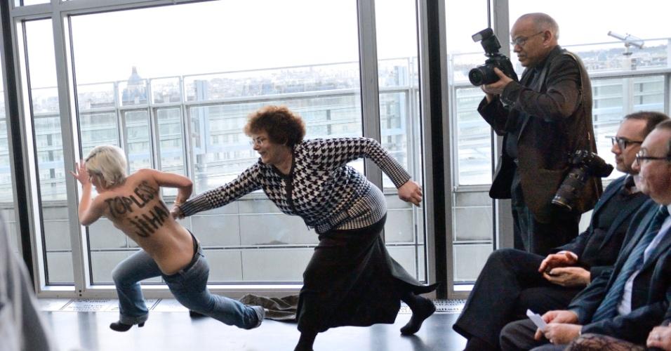 12.abr.2013 - Uma manifestante do grupo feminista Femen (à esq.) corre de mulher que tenta impedir protesto do grupo, durante entrevista coletiva em Paris do presidente da Tunísia, Moncef Marzouki, nesta sexta-feira (12). Recentemente, um líder religioso da Tunísia defendeu que uma jovem tunisiana fosse açoitada e apedrejada por ter postado nas redes sociais uma foto dela com os seios à mostra, num ato de protesto contra a situação das mulheres no país