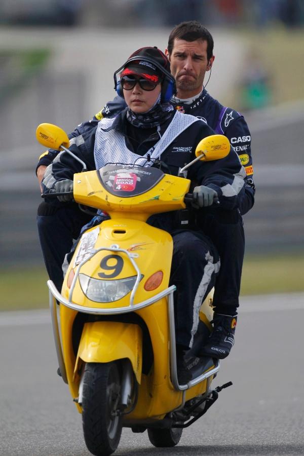 13.abr.2013 - Mark Webber pega carona para voltar aos boxes após parar sua Red Bull na pista de Xangai