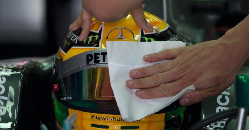 13.abr.2013 - Mecânico da Mercedes limpa a viseira de Lewis Hamilton antes de o britânico entrar na pista de Xangai para o treino de classificação do GP da China