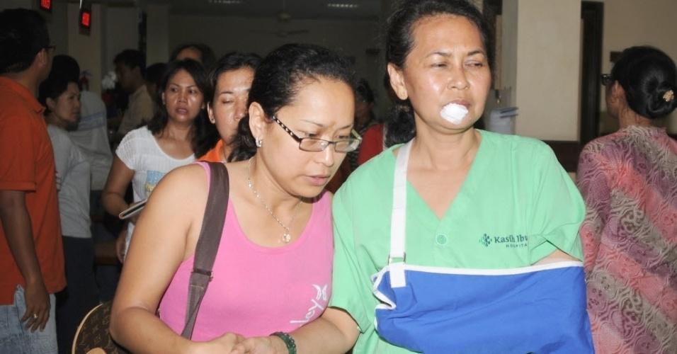 13.abr.2013 - Mulher ajuda ferido (direita) no pouso de um avião no mar ao lado do aeroporto internacional de Bali, na Indonésia. Ninguém morreu no acidente. Os feridos foram levados para um hospital na região de Kedongan, na ilha de Bali