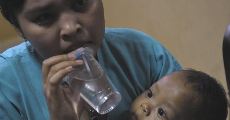 13.abr.2013 - Passageira do avião que caiu no mar após pouso mal-sucedido no aeroporto de Bali, na Indonésia, segura sua criança enquanto aguarda atendimento médico em hospital de Kasih Ibu, na ilha de Bali (Indonésia)