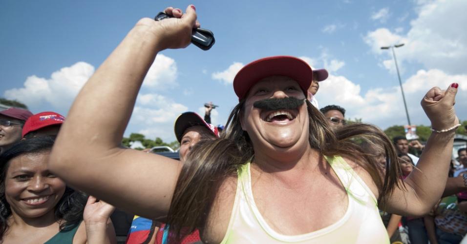 14.abr.2013 - Cidadã venezuelana demostra apoio ao candidato Nicolás Maduro utilizando um bigode parecido com o do presidente interino do país. Os cidadãos do país escolherão em pleito realizado neste domingo (14) quem será o sucessor de Hugo Chávez. A disputa está polarizada entre Maduro Henrique Capriles, candidato da oposição