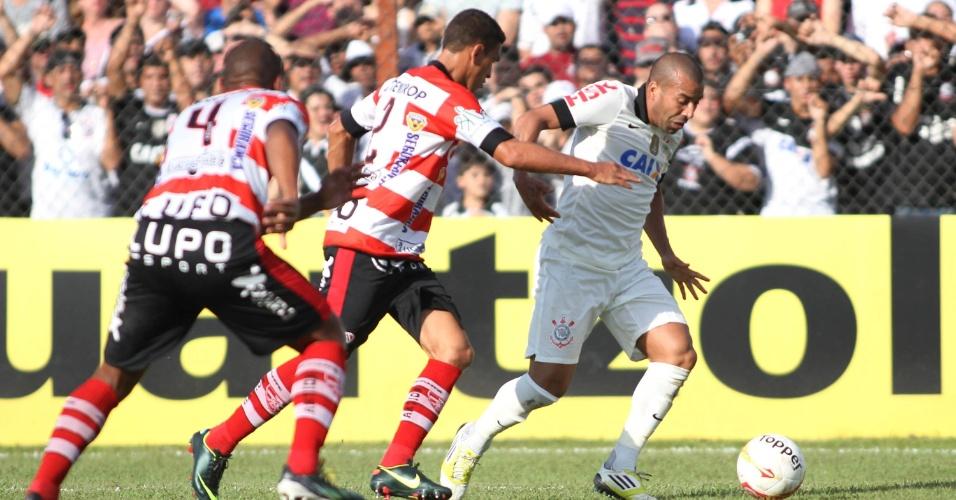 14.abr.2013 - Emerson Sheik, do Corinthians, conduz a bola cercado de perto por dois jogadores do Linense, durante partida pelo Paulistão, em Lins